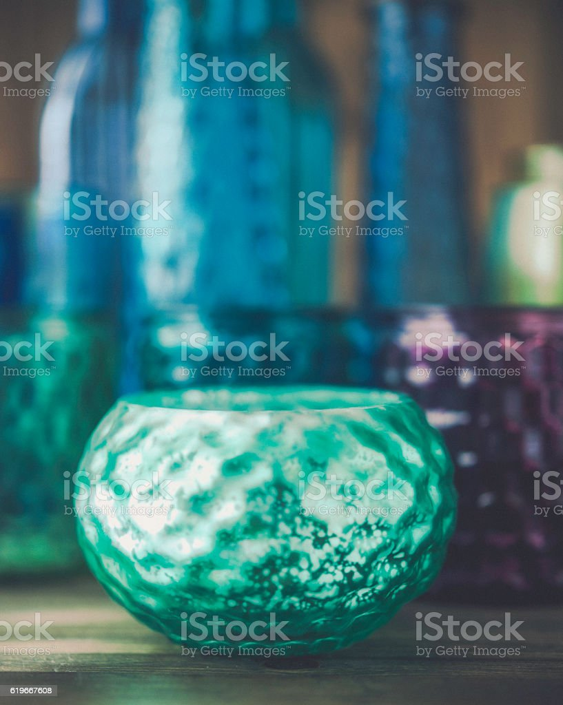 Collection of vibrant colored glass bottles, jars and bowls stock photo