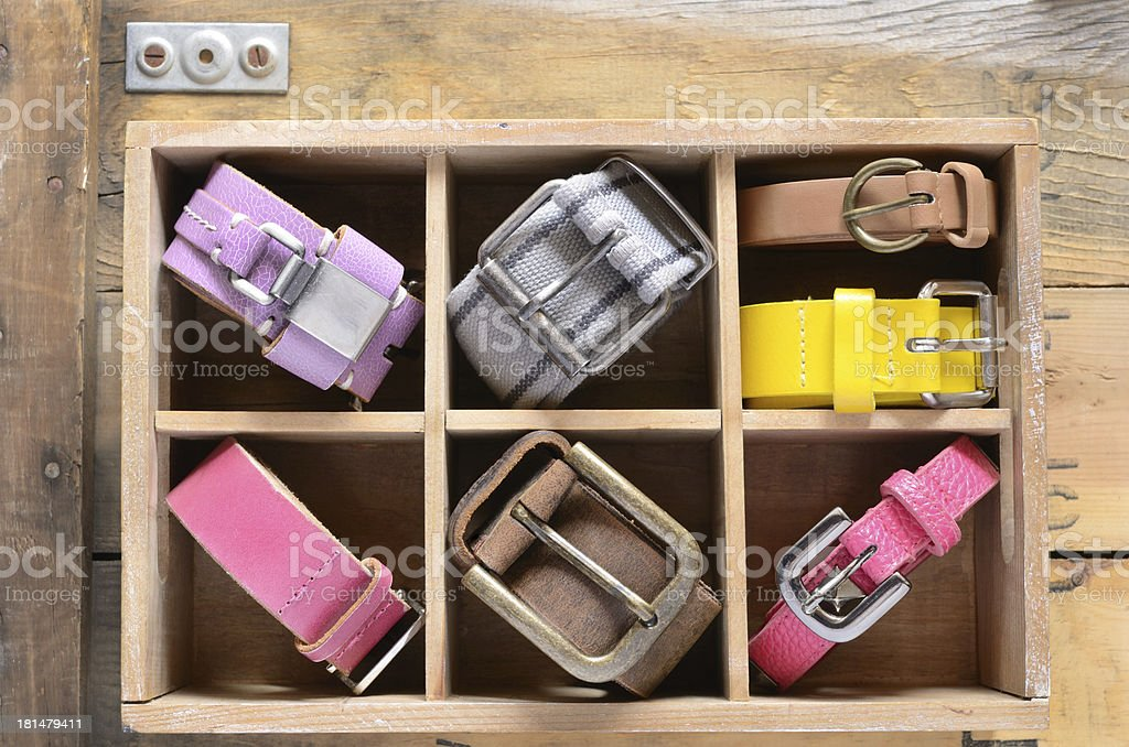 Collection of vintage colorful belts in wooden crate royalty-free stock photo