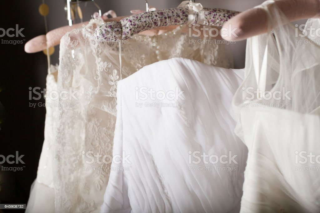 Collection of wedding dresses hanging on racks stock photo