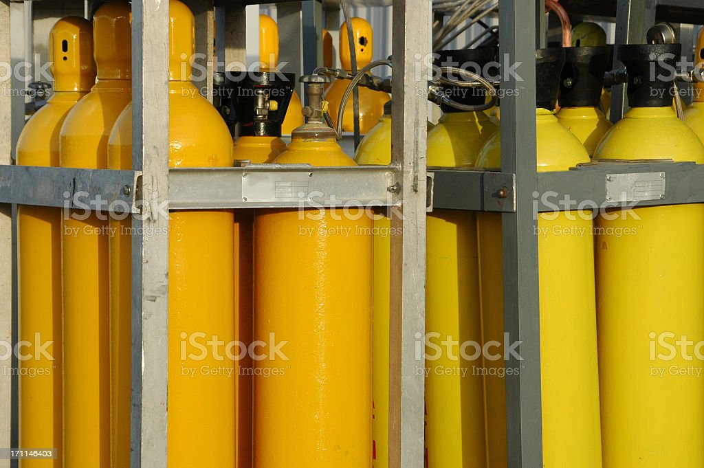 A collection of yellow gas tanks in cages stock photo