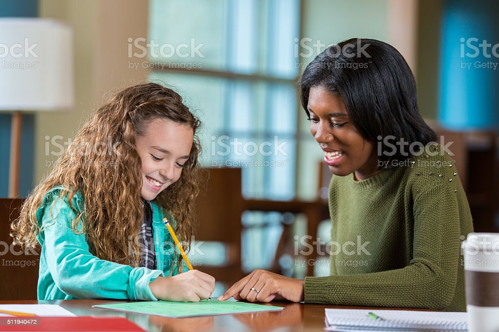 College age tutor helping elementary age girl with homework stock photo