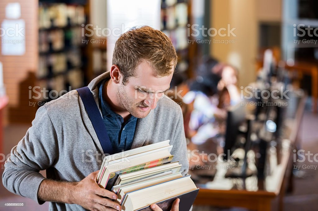 College age young man holding text books in library stock photo
