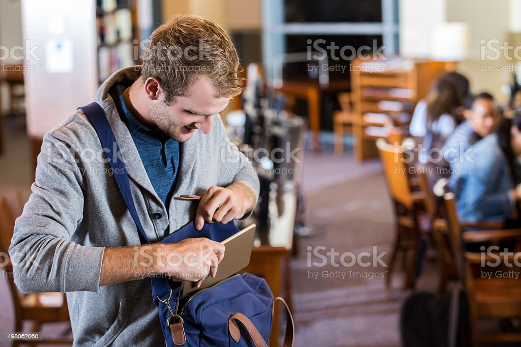 College age young man using digital tablet in library stock photo
