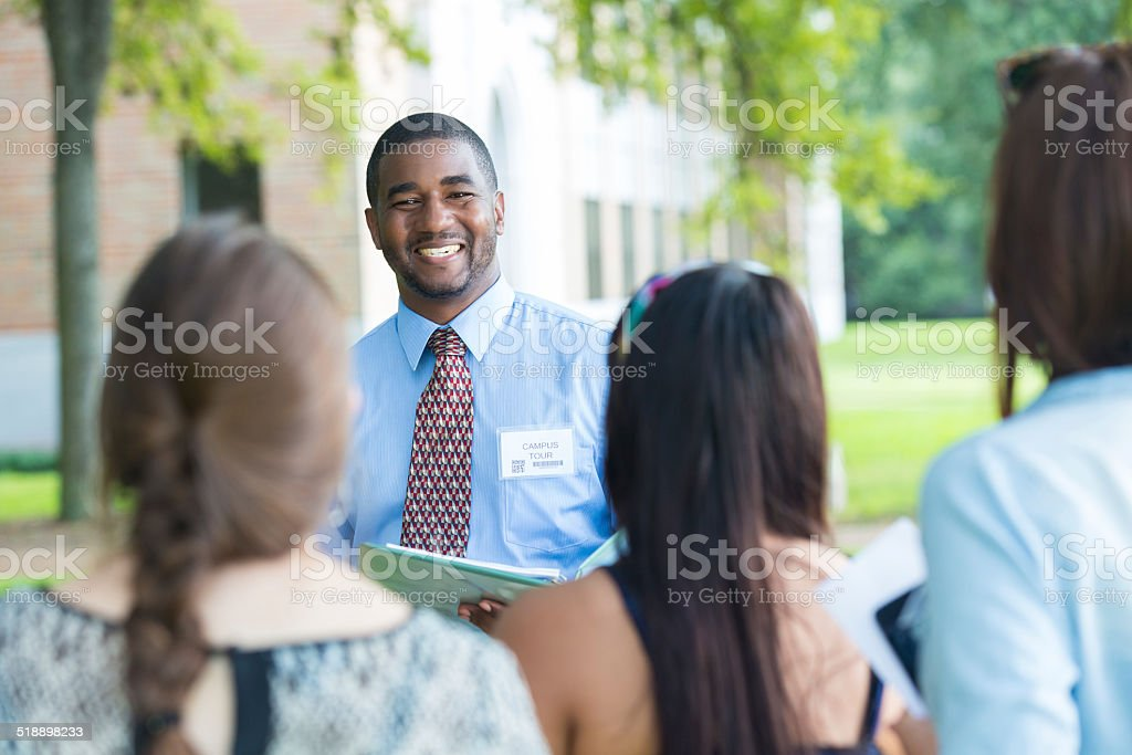 College campus tour guide talking with prospective students outdoors stock photo