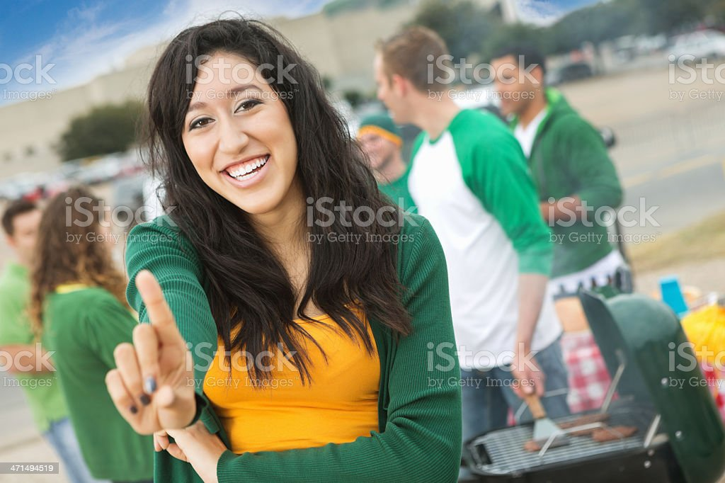 College football fan holding up 'number 1' finger while tailgating stock photo