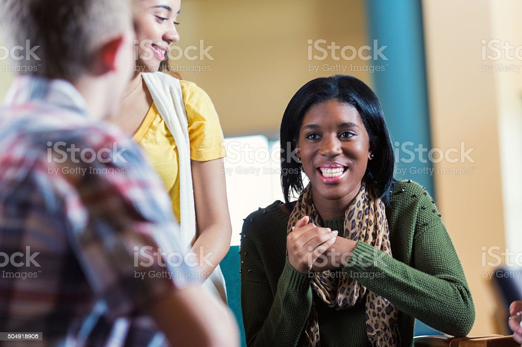College friends hanging out together in library or coffee shop stock photo