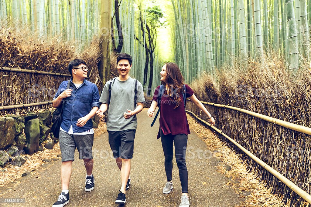 College friends taking a walk in bamboo forest, Kyoto, Japan stock photo