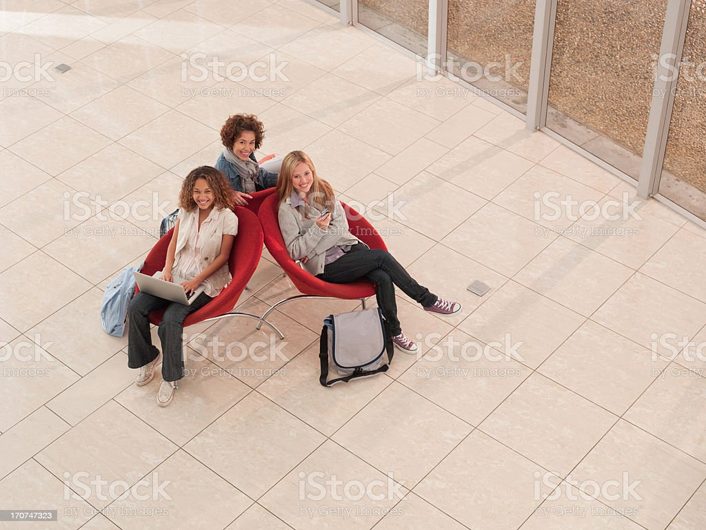 College friends using laptop and cell phone in lobby royalty-free stock photo