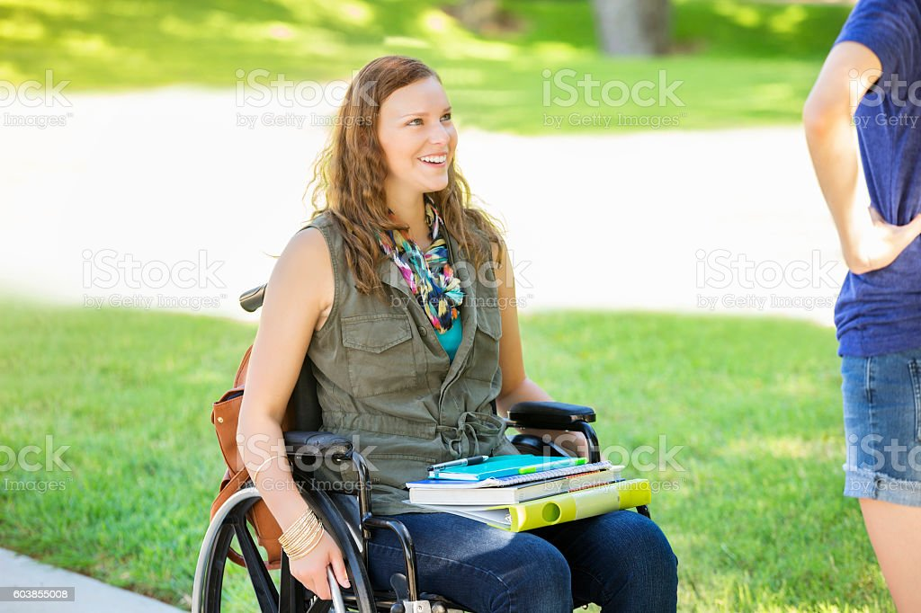 College girl in wheelchair talks with friend on campus stock photo