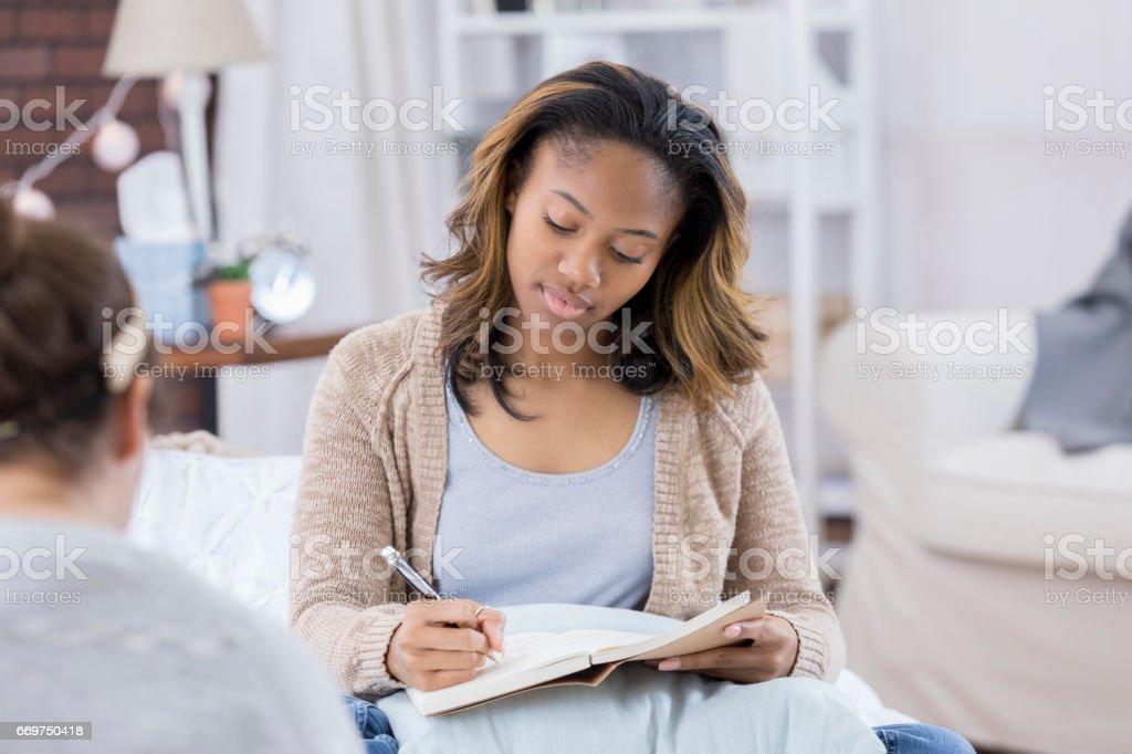 College girl journals in her dorm stock photo