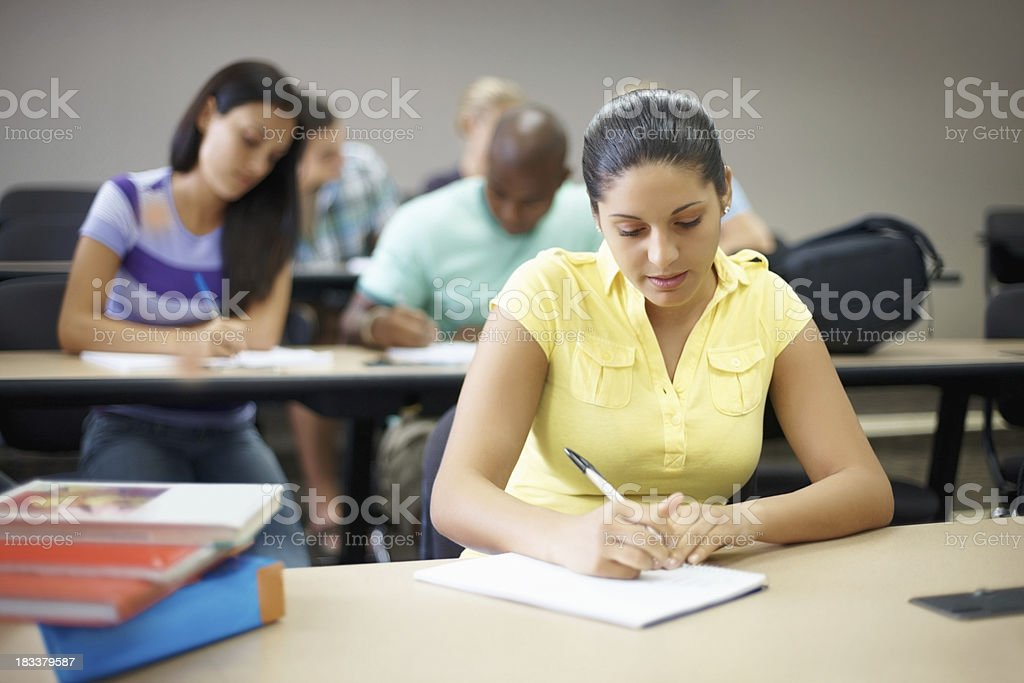 College girl studying while her classmates in the blurred background royalty-free stock photo