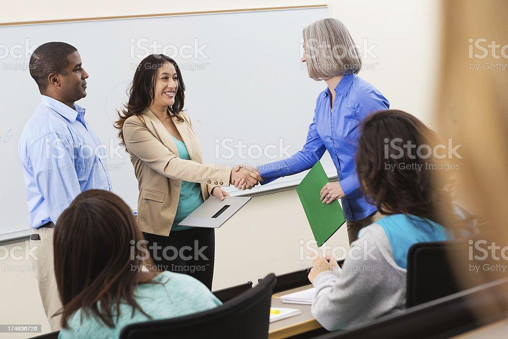College professor shaking hands with guest speaker in classroom stock photo