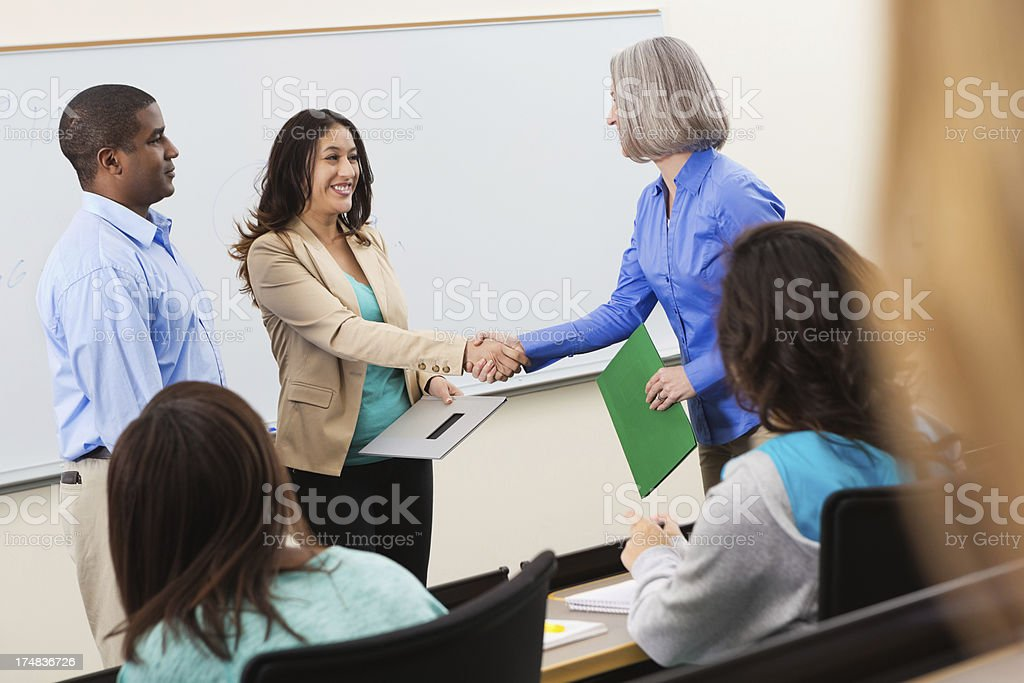 College professor shaking hands with guest speaker in classroom stock photo