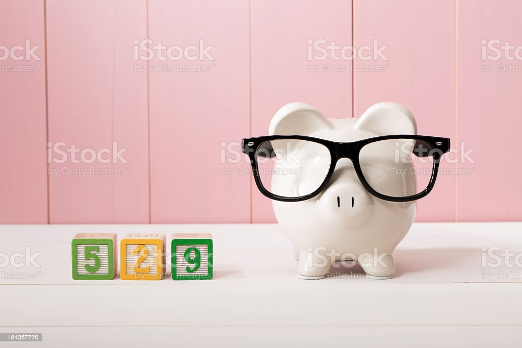529 college savings plan theme with white piggy bank stock photo