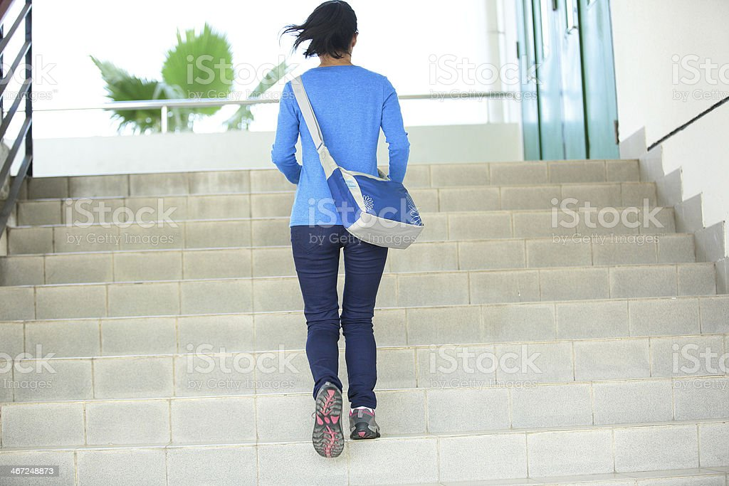 College student girl going up the stairs stock photo