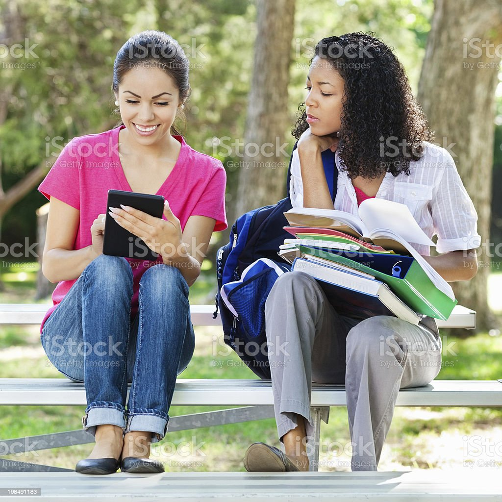 College student jealous of friend's tablet royalty-free stock photo