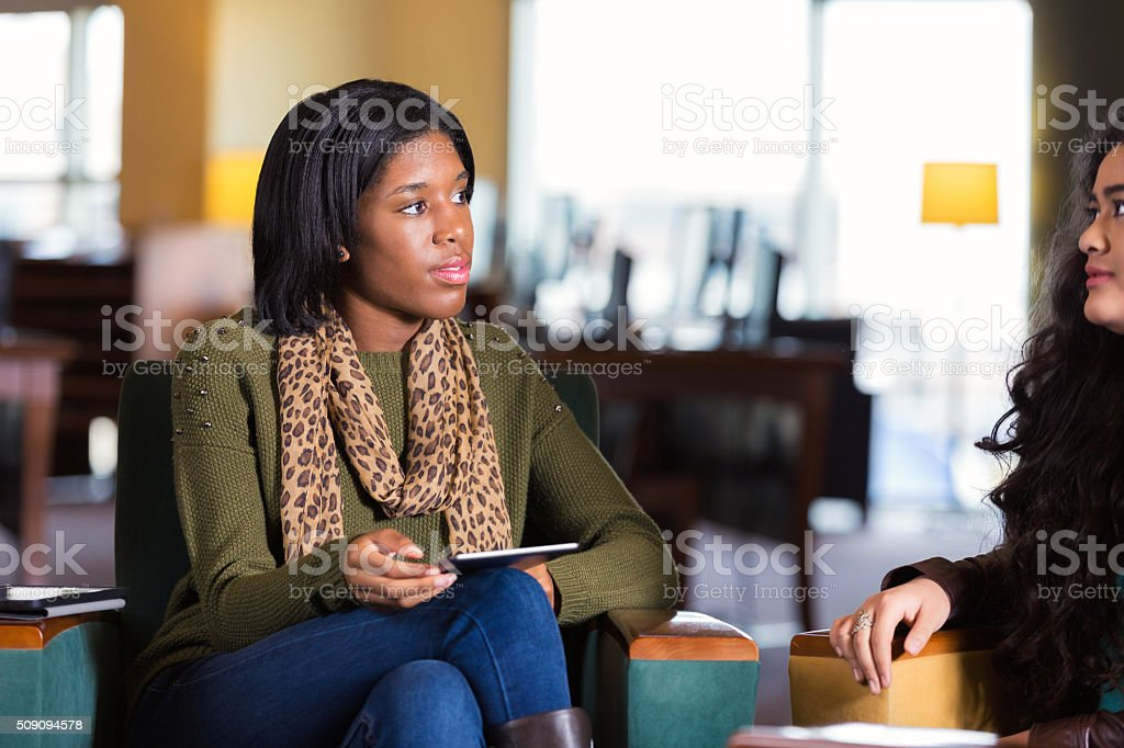 College student mentoring younger girl, meeting in library stock photo