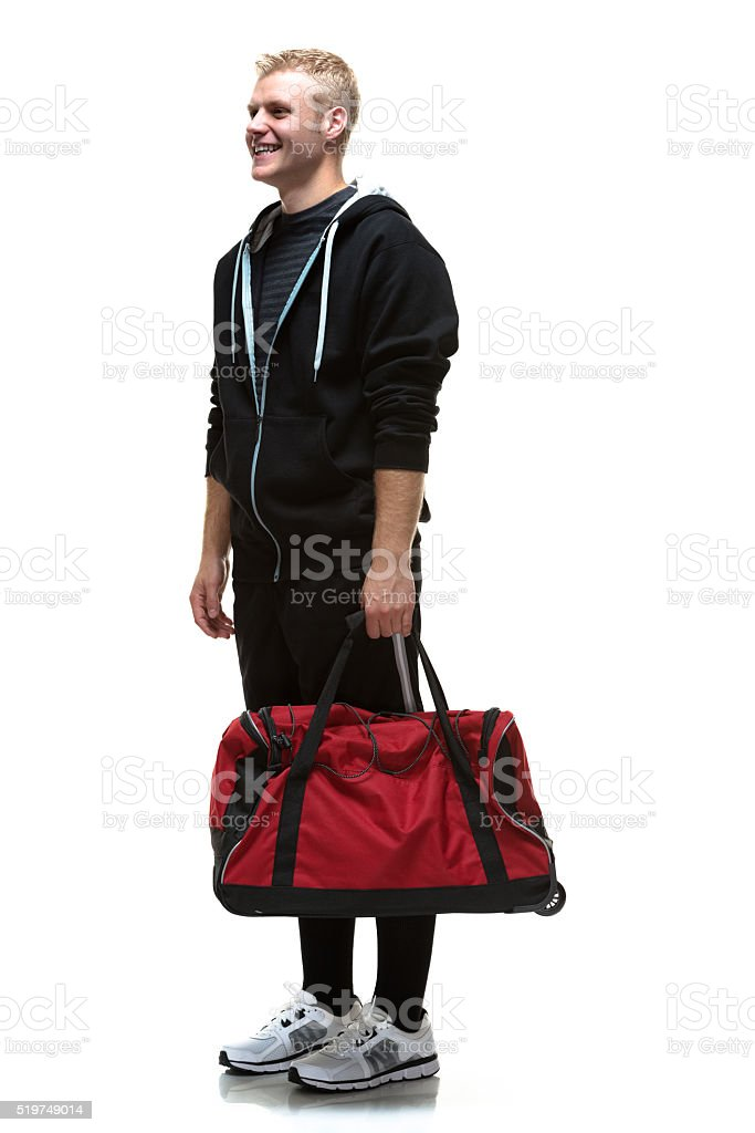 College student posing with gym bag stock photo