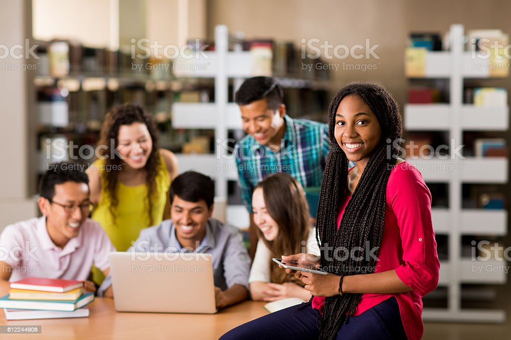 College student smiling at camera with people in background stock photo