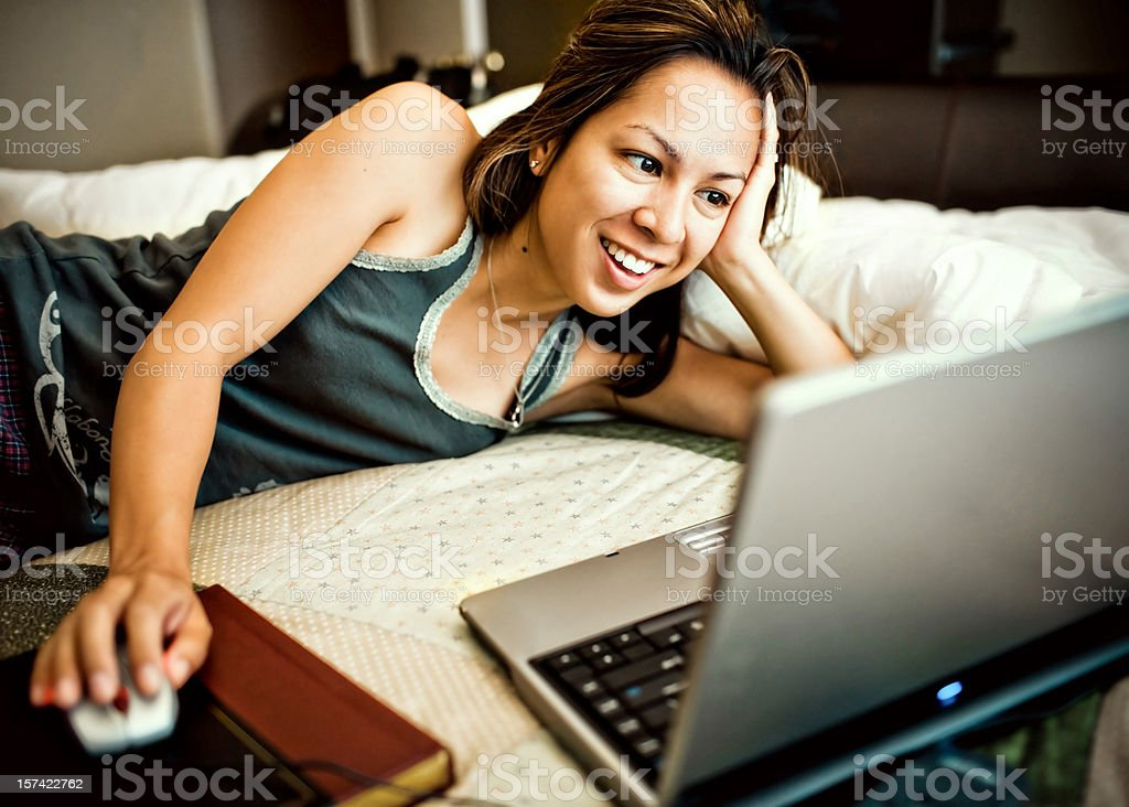 college student surfing the web on her bed royalty-free stock photo
