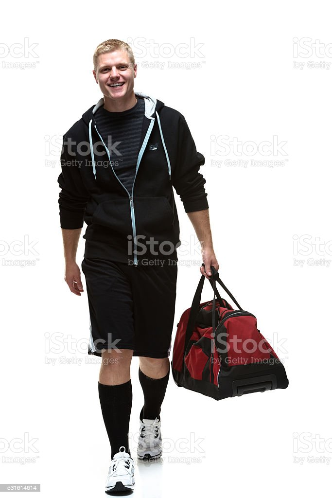 College student walking with gym bag stock photo