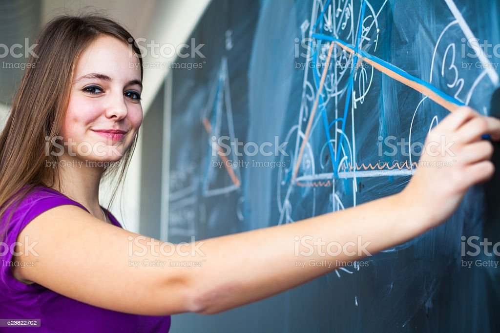 College student writing on the blackboard stock photo