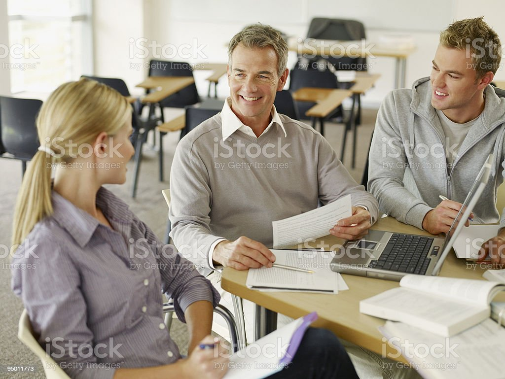 College students and professor using laptop in classroom royalty-free stock photo
