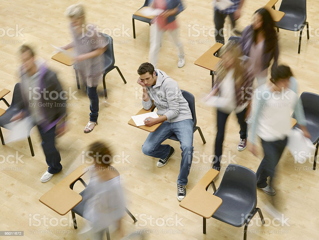 College students moving around man at desk in classroom stock photo