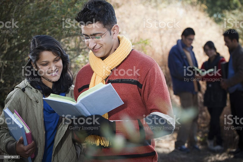 College students reading book together in nature. royalty-free stock photo