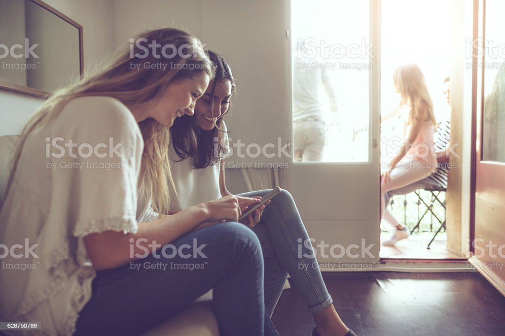 College students relaxing at home with social media stock photo