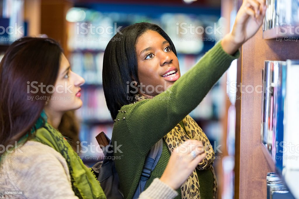College students searching for book together in library stock photo