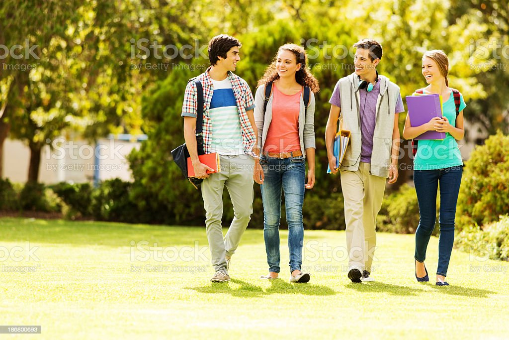 College students walking on campus lawn stock photo