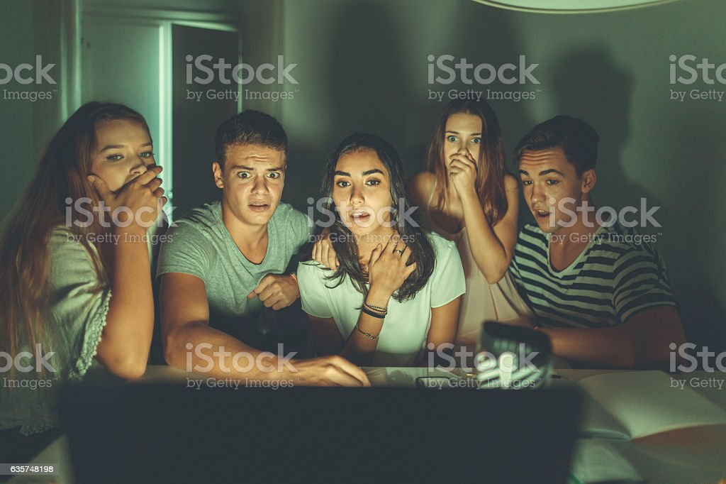 College students watching scary movie on laptop stock photo