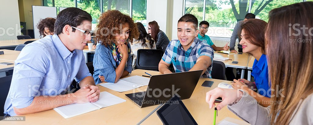 College study group brainstorming together in classroom or library stock photo