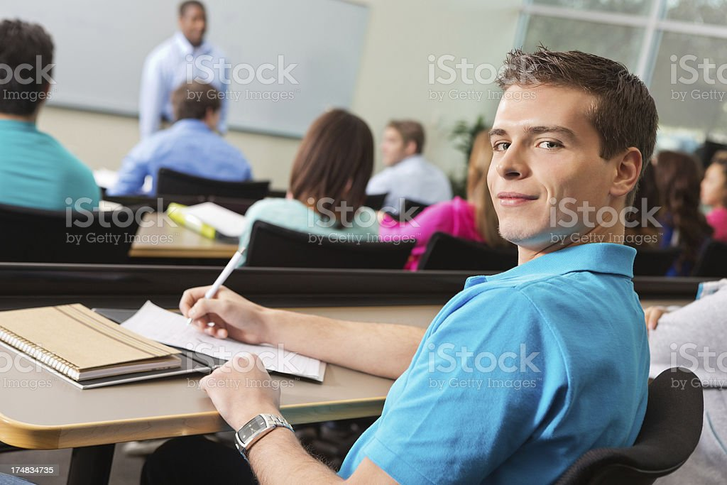Collge student looking back while taking notes in lecture hall royalty-free stock photo