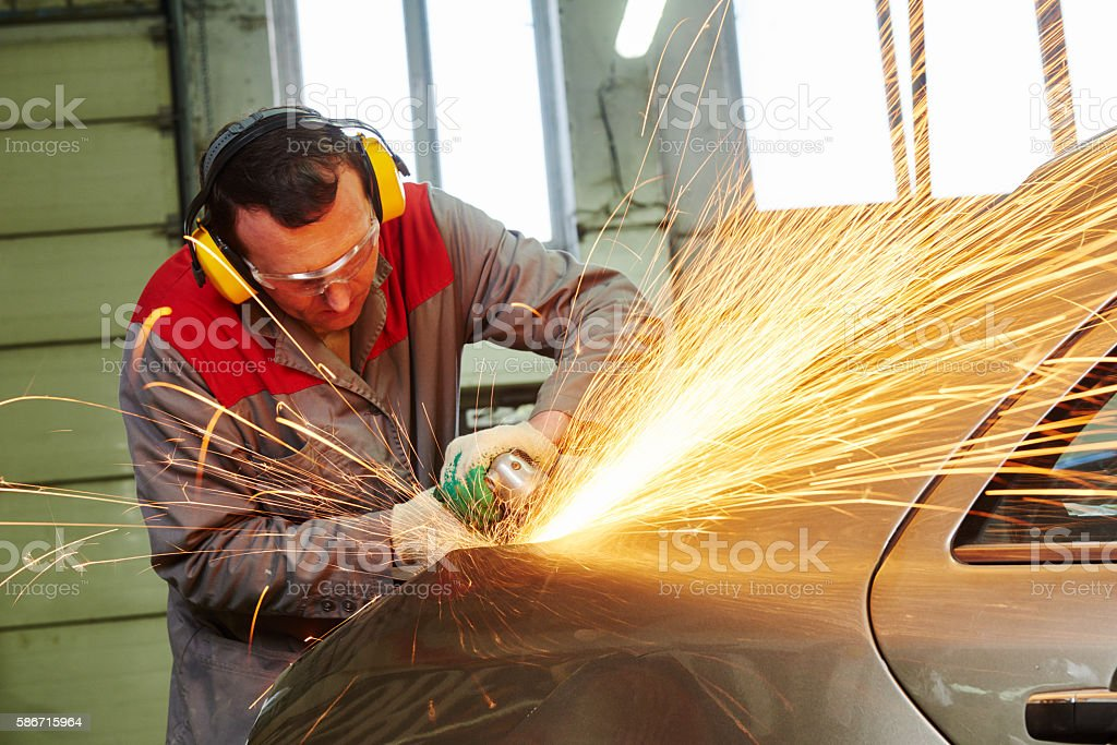 collision repairs service. mechanic grinding car body by grinder stock photo