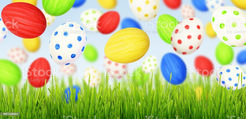 Cololrful Easter eggs falling at green grass stock photo