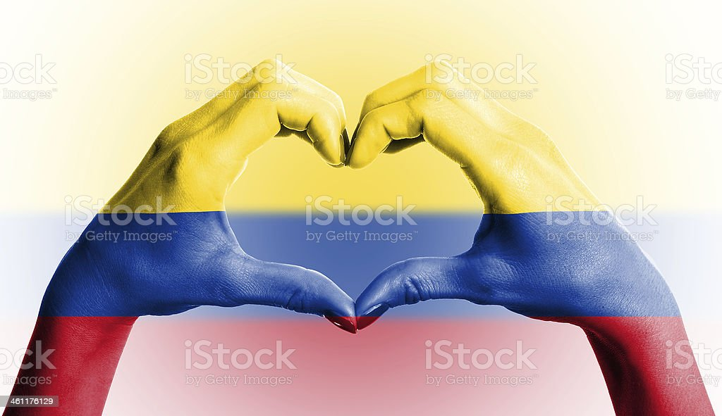 Colombian flag over heart-shaped human hands on isolated background stock photo