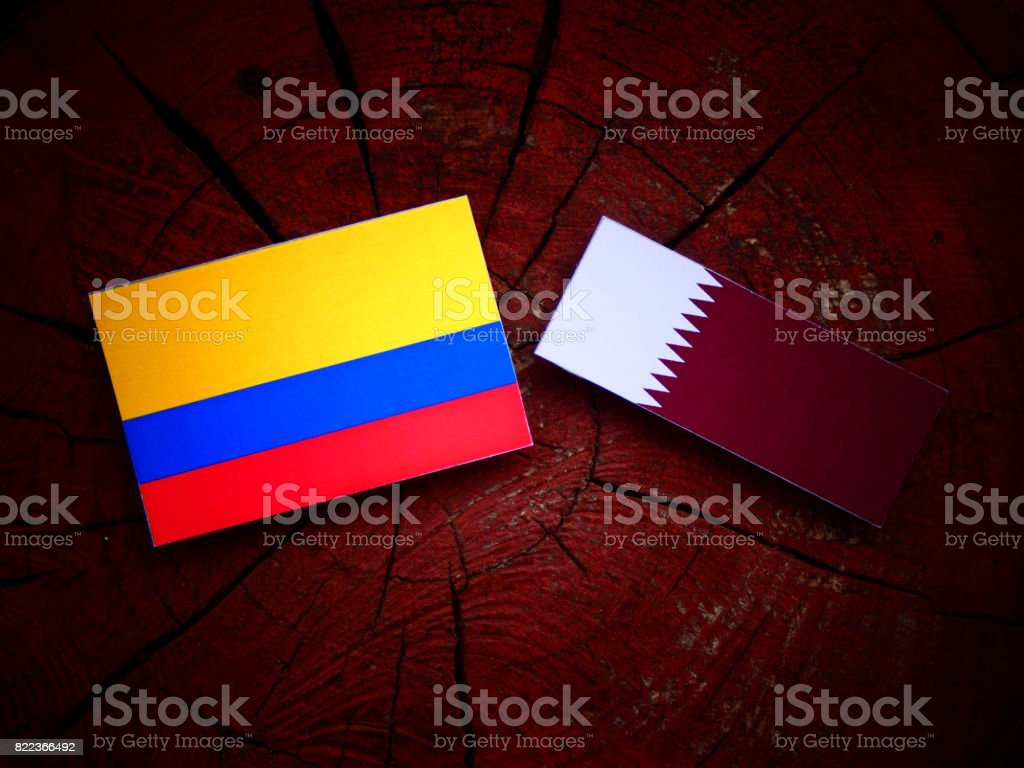 Colombian flag with Qatari flag on a tree stump isolated stock photo