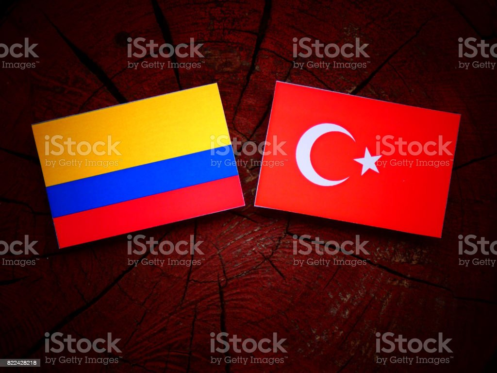 Colombian flag with Turkish flag on a tree stump isolated stock photo