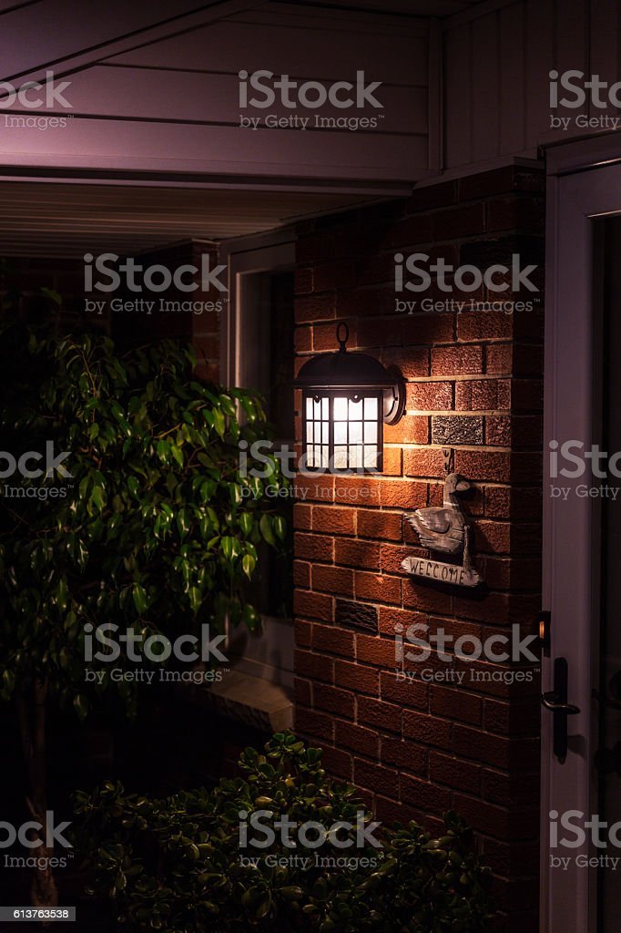 Colonial Home Entrance Front Porch Door Lamp and Welcome Sign stock photo