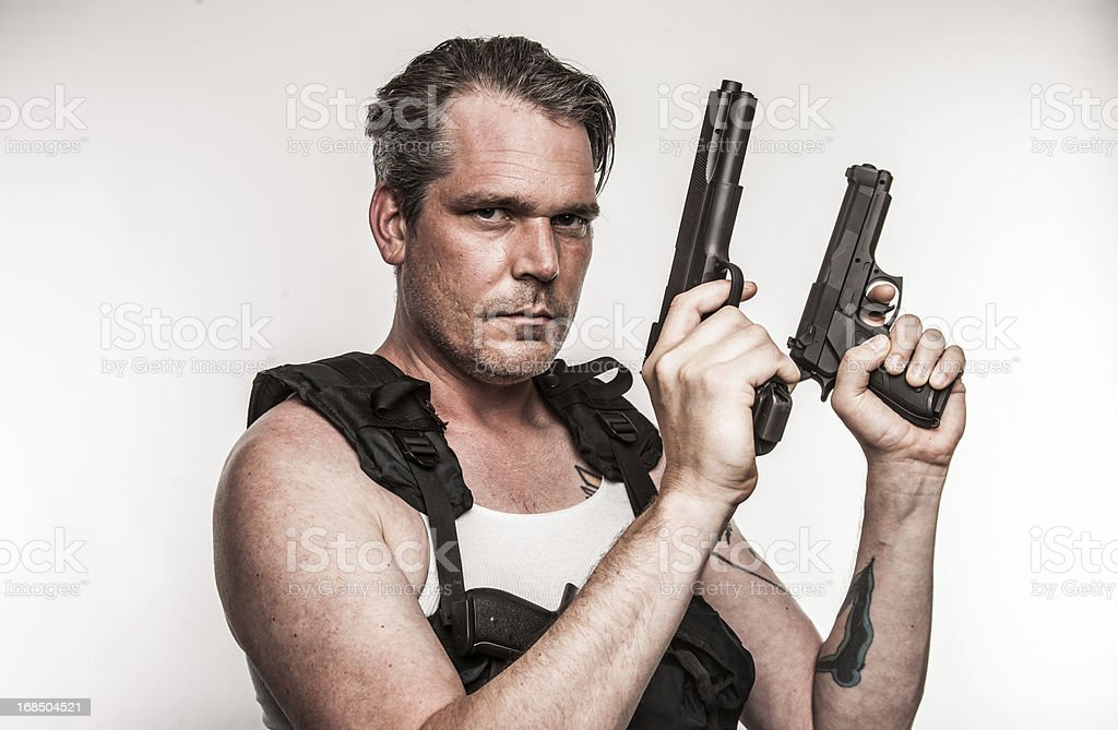 Color Action Hero Wielding Two Handguns Wearing Tactical Vest Gritty stock photo