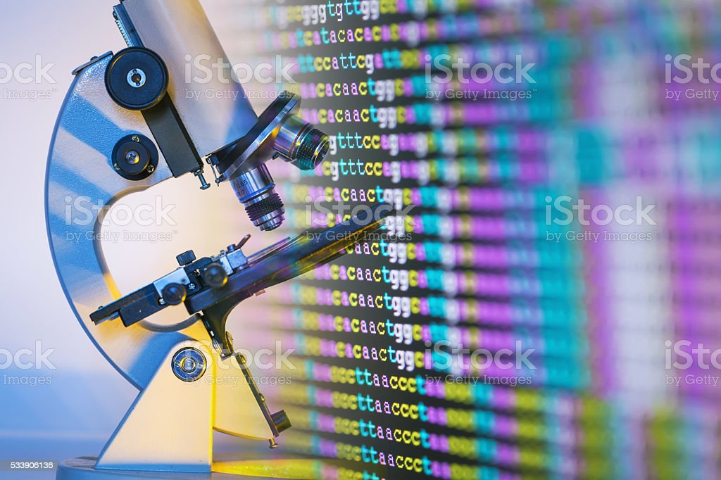 color coded DNA sequence on monitor with microscope stock photo