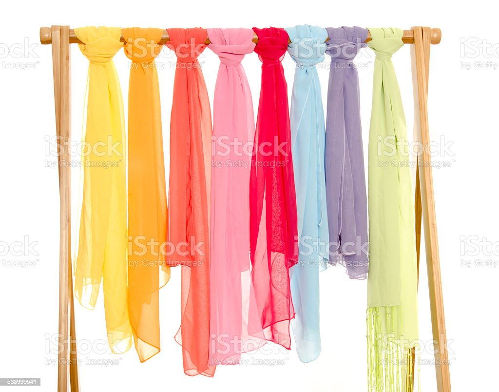 Color coordinated scarves arranged on a rack. stock photo