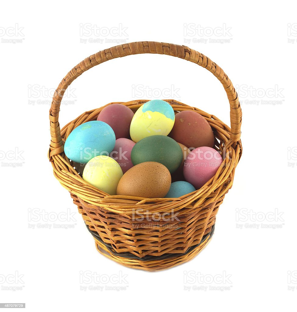 Color Easter eggs in brown basket isolated royalty-free stock photo