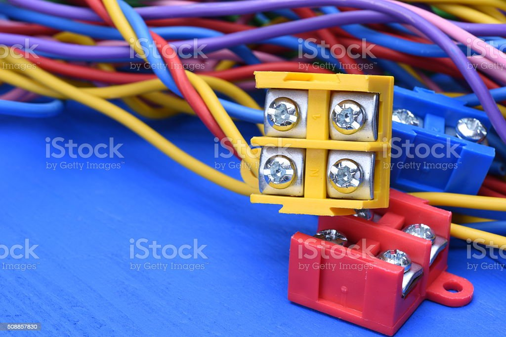 Color electric cables with terminal blocks on wooden background stock photo
