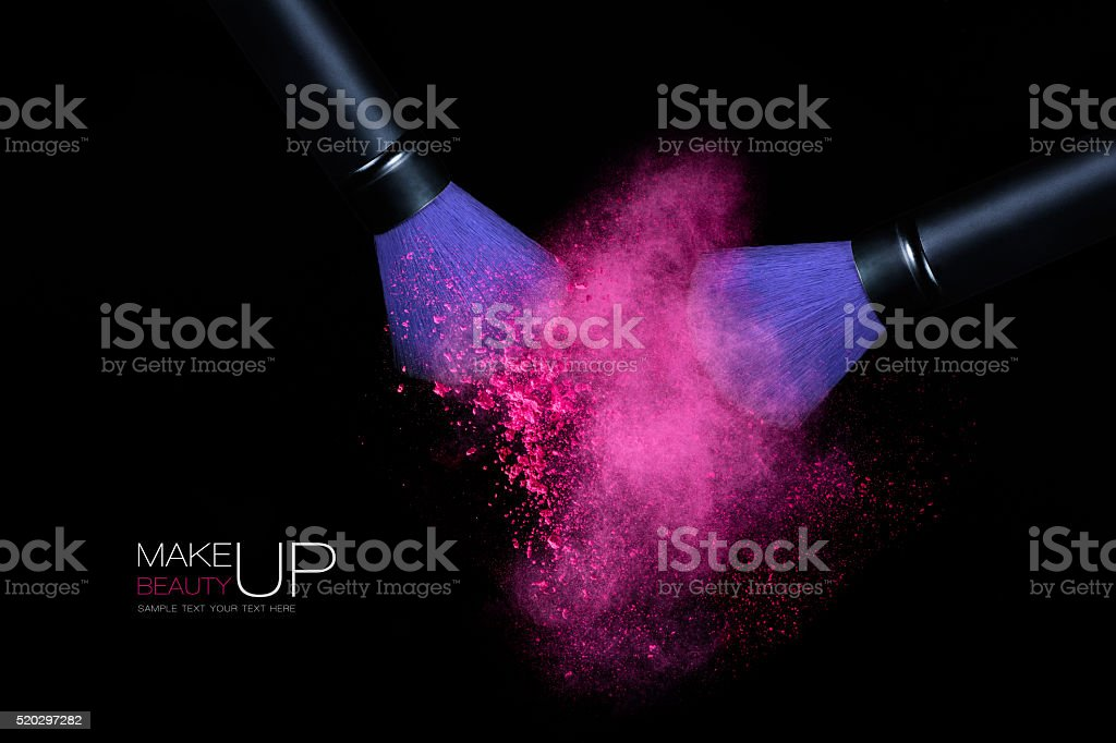 Color Explosion with Makeup Brushes Applying Powder. Isolated on black stock photo