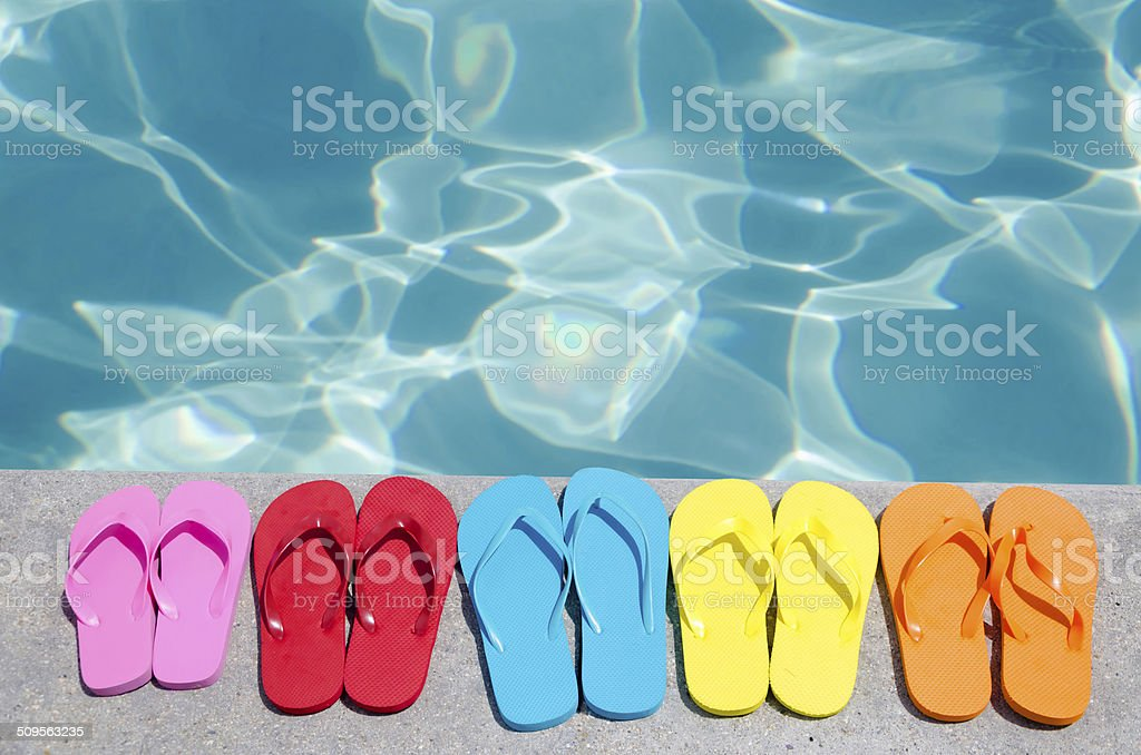 Color flip flops by the pool stock photo