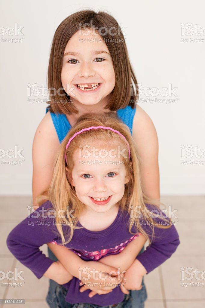 Color Image of Big Sister Giving Little Girl a Hug royalty-free stock photo