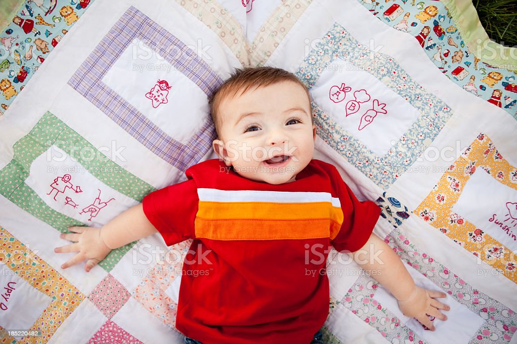 Color Image of Happy Baby Boy Lying on Handmade Quilt stock photo